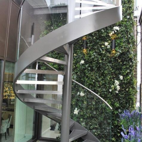Diseño de escalera caracol de metal y pasamanos con vidrio transparente
