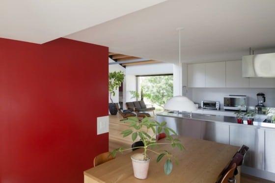 Cocina con pared roja en casa de un nivel