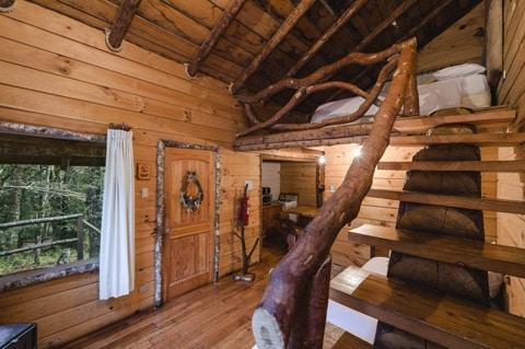 Dise o de casa peque a r stica hecha de madera y troncos for Escaleras de madera rusticas
