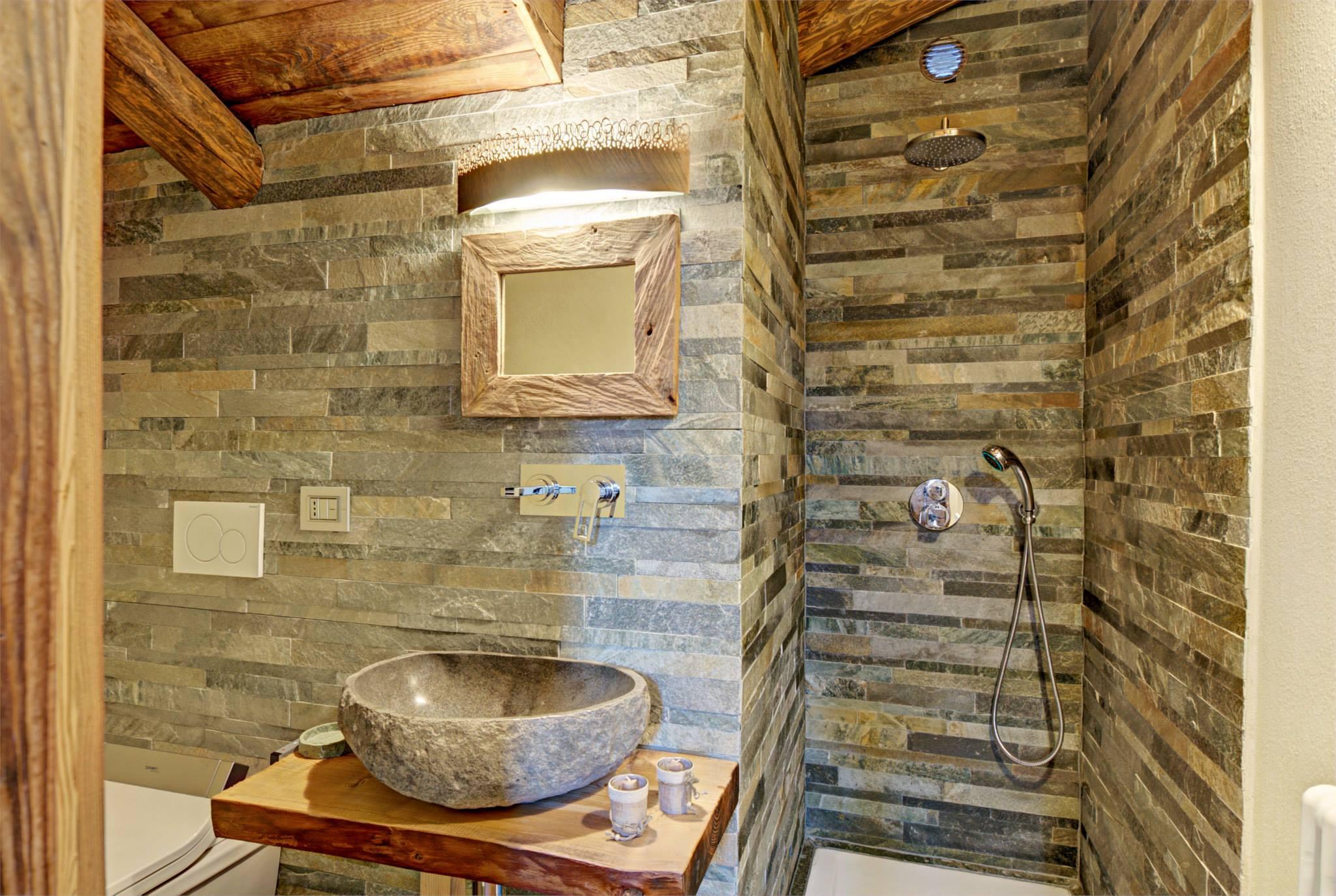 Baño De Tina Natural:Lavatorio del cuarto de baño de piedra reposa sobre una mesa de