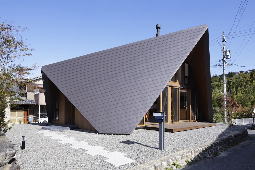 Casa de dos pisos con techo tipo origami para protecci n for Formas de techos para casas