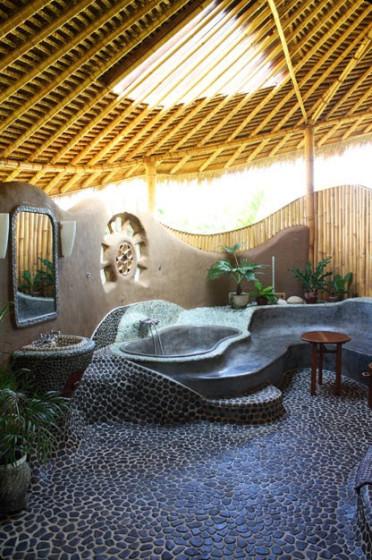 Diseño original de cuarto de baño rústico con bambú, piedra rodad y barro