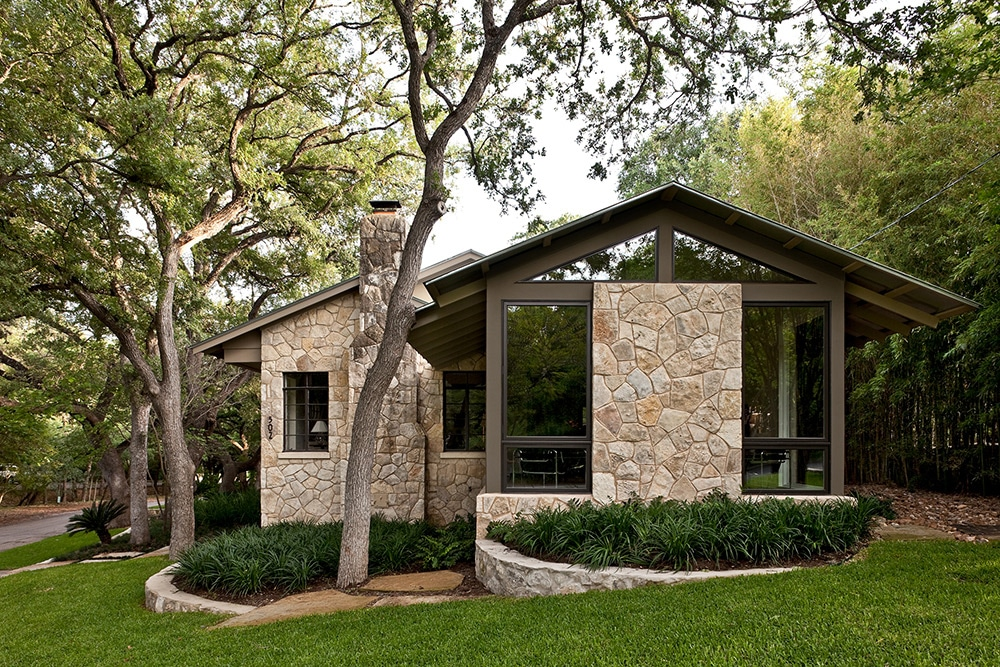 fachada de casa de piedra con jardineras ovaladas
