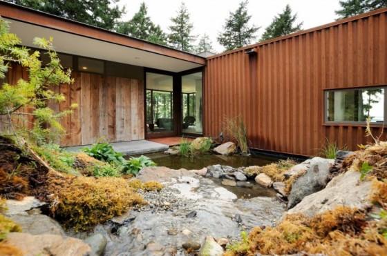 Fachada posterior de casa rural con un pequeño diseño de jardín