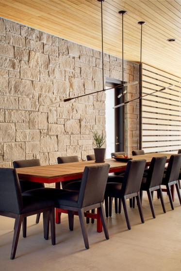 Diseño de comedor con paredes de piedra y techo de madera