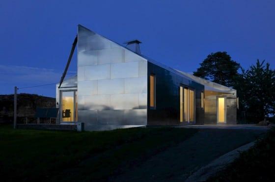 Fachada de casa de metal por la noche iluminada internamente
