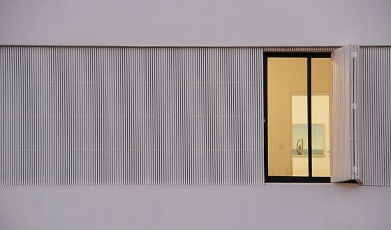 Detalle de ventanas con persianas exteriores de madera verticales