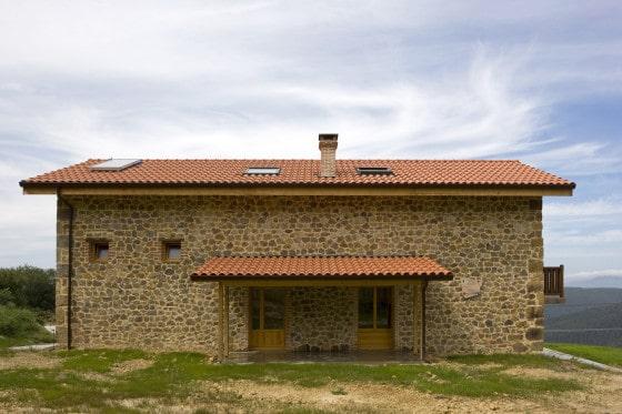 Fachada de pequeña casa rústica  de piedra